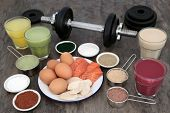Weight training equipment for body builders with dumbbell weights, high protein meat, fish and dairy poster