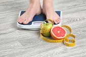 Woman standing on scales near fruits and measuring tape on wooden floor. Concept of weight loss poster