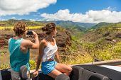 Road trip vacation car couple taking pictures of Hawaii nature landscape with smartphone camera app. poster