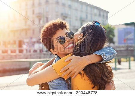poster of Happy meeting of two friends hugging in the street. Smiling girls friends laughing and hugging in th