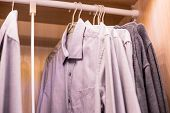 Many Shirts Hanging On A Rack.row Of Mens Suits Hanging In Closet. Concept Of Buy And Sell, Business poster