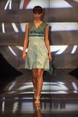 Fashion model in green toned dress walking down the runway