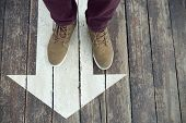 White Arrow Sign On Wooden Floor. Mans Legs Standing On Arrow Sign Painted On The Floor. Direction S poster