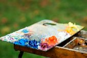 Art Palette On Nature Blured Background. Artist Paints A Picture Of Oil Paints. Dirty Art Palette. P poster
