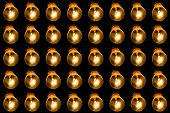 Glowing Lamps On A Black Background. Many Lamps In A Row Shine With Yellow Light poster