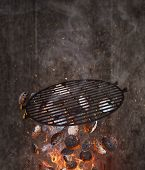 Kettle grill with hot briquettes and cost iron grid flying in the air. Freeze motion barbecue concep poster