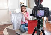 Asian Young Female Blogger Recording Vlog Video With Review Cloths T-shirt At Home Online Influencer poster