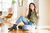 Young beautiful woman sitting on the floor at home relax and smiling with eyes closed doing meditati poster