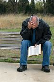 stock photo of sad man  - Sad looking man sitting on bench while holding his bible - JPG