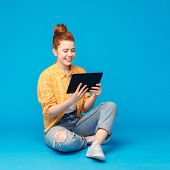 technology and people concept - red haired teenage girl in checkered shirt and torn jeans using tabl poster