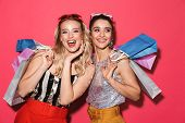 Photo of two shopaholic women 20s in trendy outfit holding colorful shopping bags isolated over red  poster