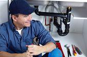 Smiling plumber repairs a sink. poster