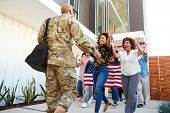 Family welcoming back millennial black soldier   returning home,low angle view poster