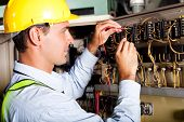stock photo of electricity meter  - male electrician testing industrial machine - JPG