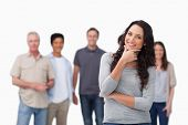 picture of thinkers pose  - Smiling woman in thinkers pose and friends behind her against a white background - JPG