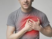 Young Man Having Heart Ache, Holding Hand On Chest. Heart Attack Or Stroke poster