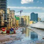 image of malecon  - Havana during a hurricane with big waves crashing against the seaside wall and debris on the street - JPG