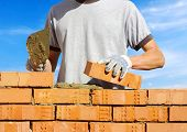 foto of bricklayer  - bricklayer laying bricks to make a wall - JPG