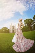 A woman like a princess in an vintage dress before the magic castle