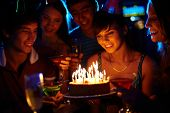 foto of congrats  - Portrait of joyful girl looking at birthday cake surrounded by friends at party - JPG
