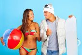 Portrait of happy girl in bikini with ball looking at handsome man in winterwear holding snowboard and both showing thumbs up