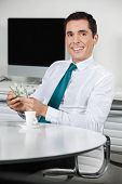 Happy businessman with many dollar bills in his office