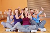 Happy smiling group in fitness center holding their thumbs up in a gym
