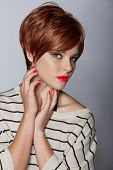 image of pixie  - beautiful young woman with red hair wearing short pixie crop hairstyle on studio background - JPG