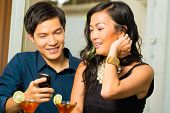 image of shy woman  - Asian man is flirting with woman in a bar while having drinks - JPG