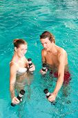 Fitness - a young couple - man and woman - doing sports and gymnastics or water aerobics under water