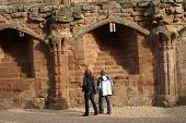 Tourists/ Young Couple Looking At Wall Of A Ruined Castle poster