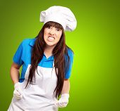 portrait of a female chef clenching on green background