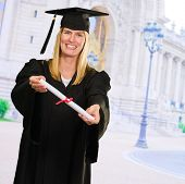 Happy Graduate Woman showing Certificate against a monument as a background, outdoor