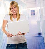 Happy Woman Looking At Laptop in a passageway, indoor