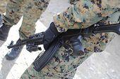 homem em camuflagem segurando uma arma de airsoft