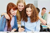 Three happy women checking social media with a smartphone in university