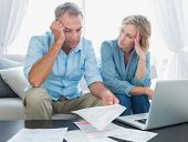 pic of crunch  - Worried couple using their laptop to pay their bills at home in the living room - JPG