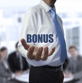 Elegant businessman holding the word bonus in front of a business team