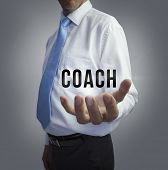 Businessman holding the word coach on grey background