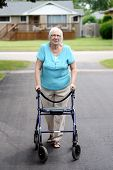 stock photo of street-walker  - senior woman with walker in the driveway - JPG