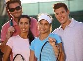 Retrato de sorridentes equipe jovem de tênis na quadra de tênis.