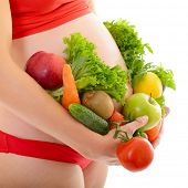 Beautiful pregnant woman in red with fresh fruits and vegetables, healthy life concept, isolated ove