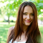 young beautiful lady outdoor portrait, girl with long brown hair posing in summer park