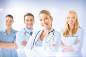 healthcare and medicine concept - female doctor in front of medical group