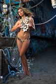 Sexy blond model posing topless wearing seashell necklace and bikini bottom