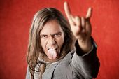 stock photo of american indian  - Closeup Portrait of Handsome Young Man with Long Hair Making Hand gesture and Sticking Out Tongue - JPG