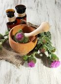 pic of scottish thistle  - Medicine bottles and mortar with thistle flowers on wooden background - JPG