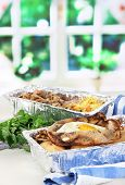 Food in boxes of foil on napkin on wooden board on window background