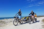 foto of tandem bicycle  - Family on a beach bicycle ride together - JPG