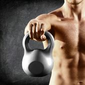 Kettlebell dumbbell - fitness man lifting weight kettle bell training crossfit. Muscular shirtless m
